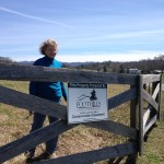 Gail at the front gate with FLC conservation easement sign.