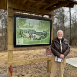 Dr. Craig Jarvis stands beside the park's trail sign